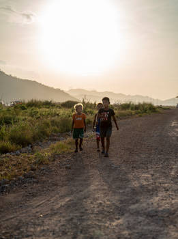 Three kids walking along a dusty dirt road