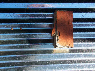 brick on corrugated steel with raindrops