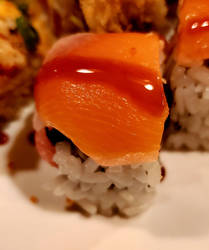 Spicy tuna with avocado and topped with salmon.