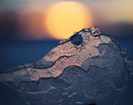The shy sun hiding behind the mountain of ice
