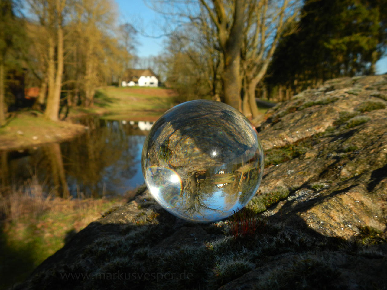 Glass sphere on rock at a pond by Acrylicdreams