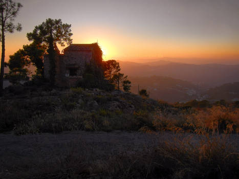 Sunset behind a stone house