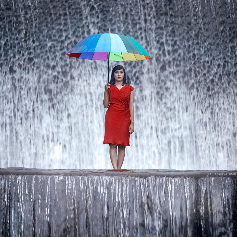 девушка с зонтом и пядом с водопадом