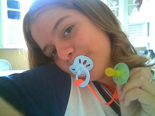 Naked women with pacifier in mouth consider