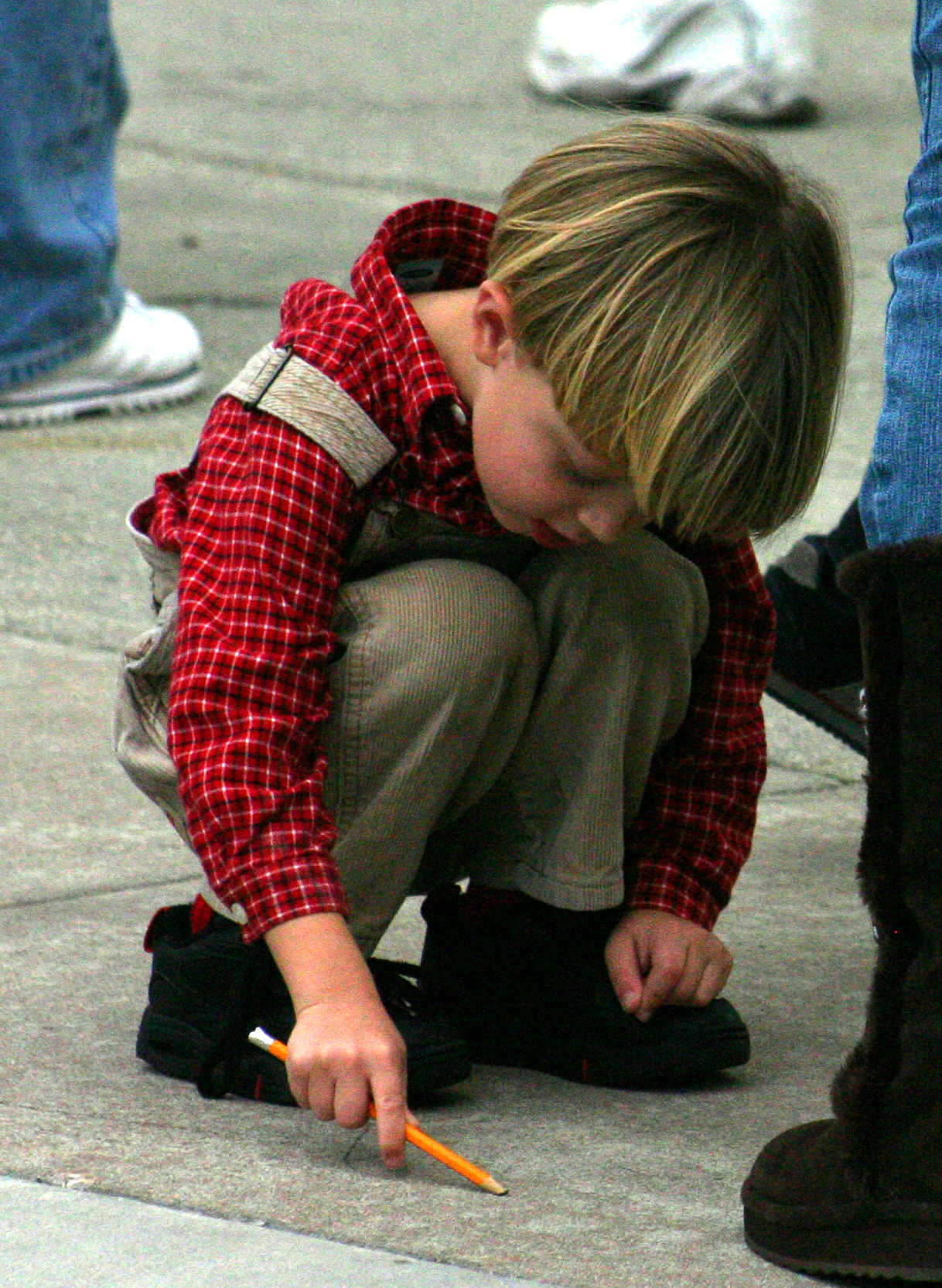 Little Boy Drawing on Ground