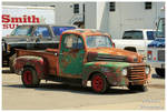 A Rusty Ford Truck With Red Wheels