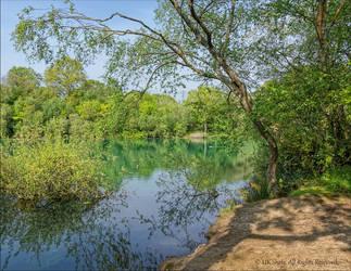 Emerald waters at Creekmoor Tarn, Dorset by UK-Shots