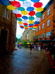 A flight of Umbrellas high above the street
