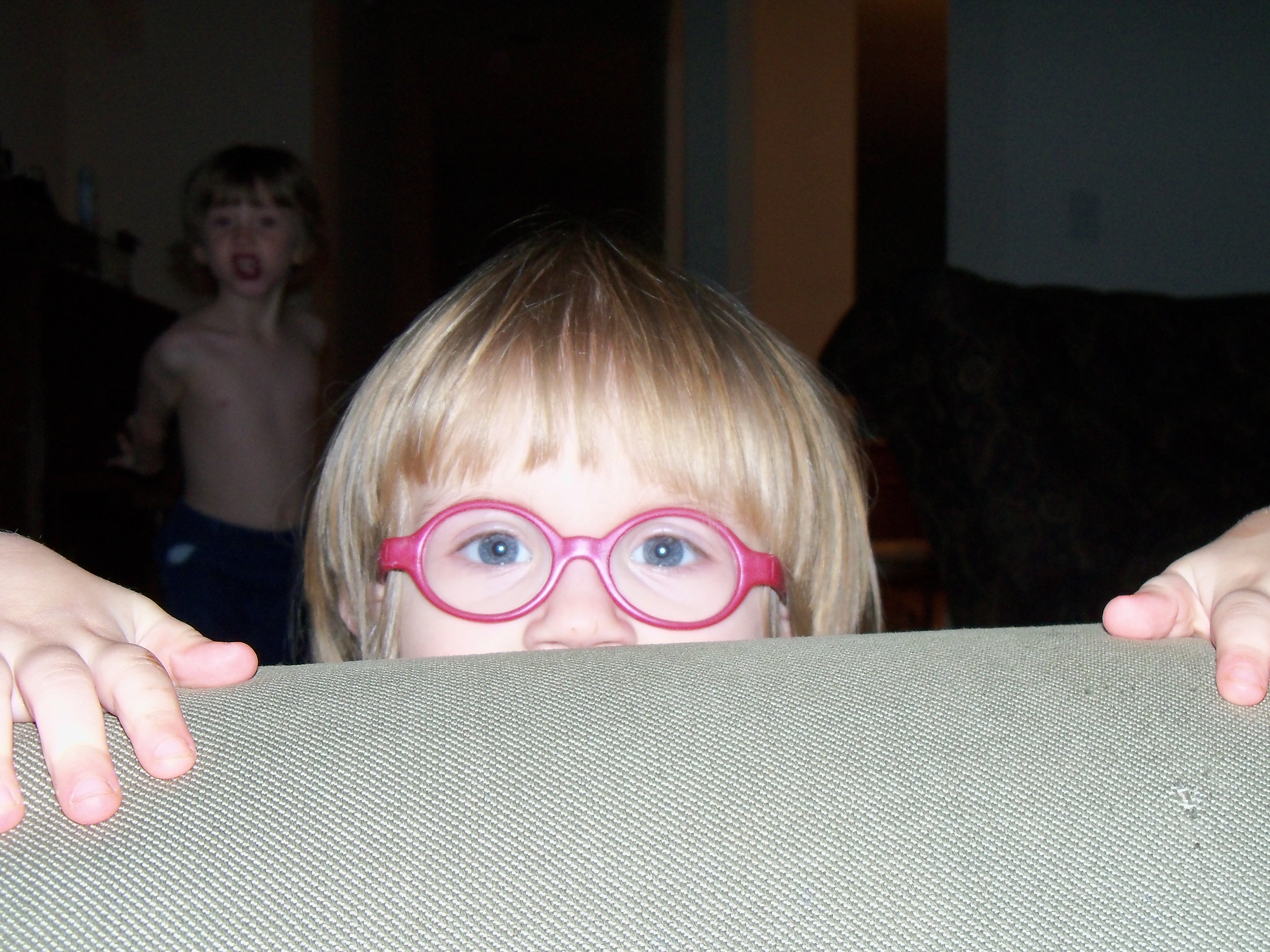 Child Peeking Behind Couch