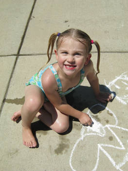 Blonde Girl With Pig Tails Drawing With Chalk