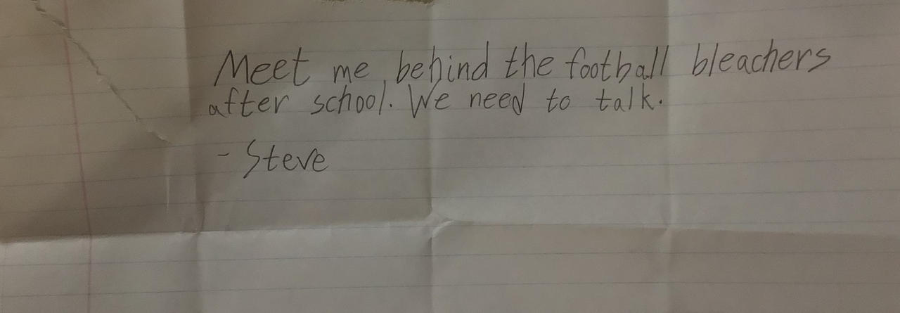 Steve's note to Billy which reads: Meet me behind the football bleachers after school. We need to talk. Steve.