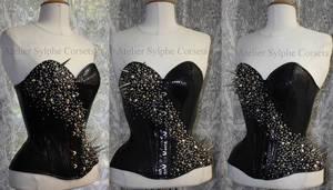Spikes, studs, strass on black snake patent corset