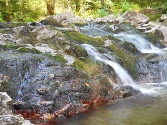 Water falling among the mossy and redish rocks
