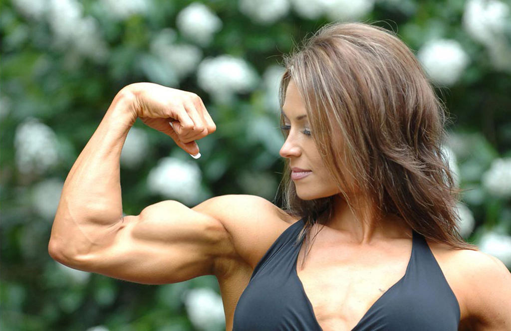 Sexy curvy muscle girl flexes biceps boobs