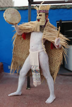 mexica man in rain cape playing drum