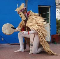 kneeling Mexica man in raincoat playing drum