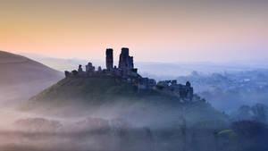 Corfe Castle Shrouded in Mist at Sunrise in Dorset