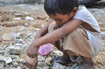 Child playing rocks by pauljunelaquino