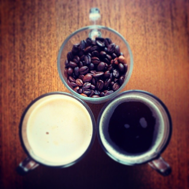three cups: beans, cream, and black coffee
