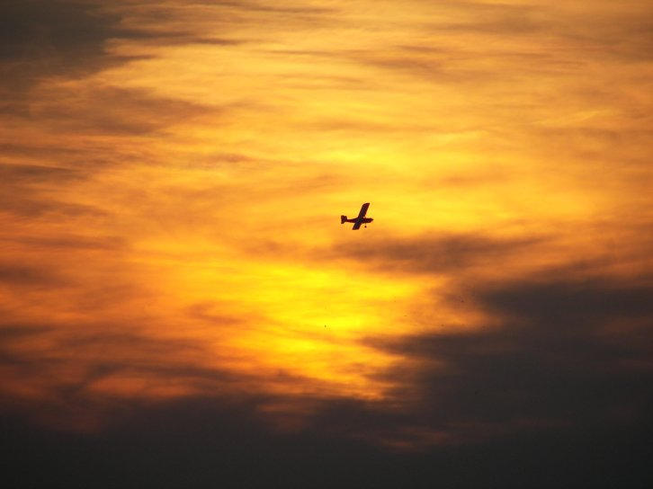 plane in the sky of fire by Littlelion225
