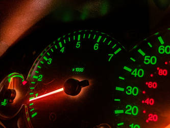 image thumbnail showing a lit instrument cluster for a car. the background is dark, as it is night. the rpm and mph numbers are lit in green, the alternate metric units are lit in red, and the needles are lit orange.