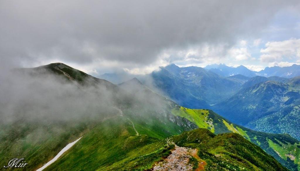 Mountains peaks in the fog by miirex