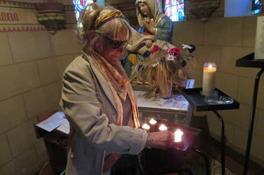 Ingeline lighting a candle in church