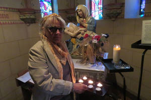 Ingeline lights a candle by mother Mary