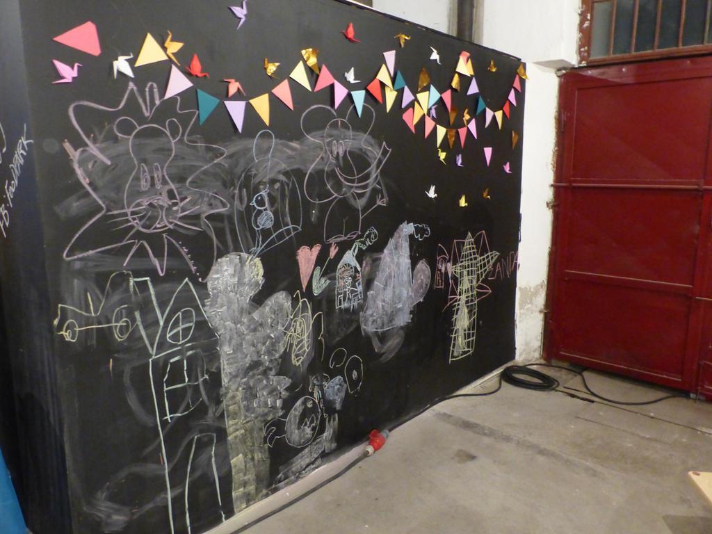 Stěnu v rohu postavených záchodů tvořila tabule, na kterou bylo možno kreslit křídou. Již první den byla pokreslena křídami, žádné křídy však u tabule nebyly, takže možná šlo jen o tematickou ozdobu.