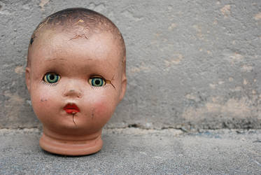 Antique doll head against cement