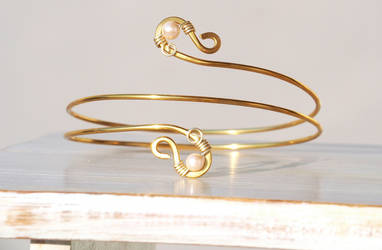 Gold tone arm band with champagne color pearls