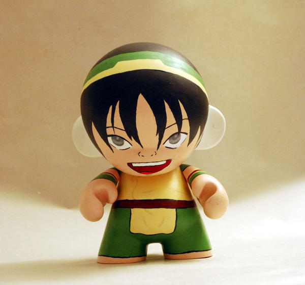 A small, handpainted toy of Toph that has shrunk her proportions but is still very cute and Toph-like