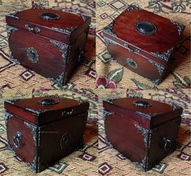 A wooden tarot box with a green cabochon