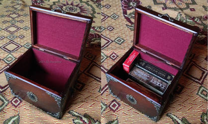 A wooden tarot box with a green cabochon - inside
