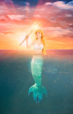 Mermaid in the ocean by sunset