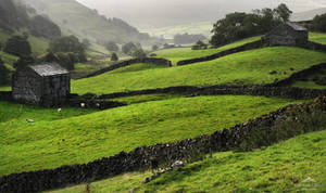 Two dark stone barns in a valley