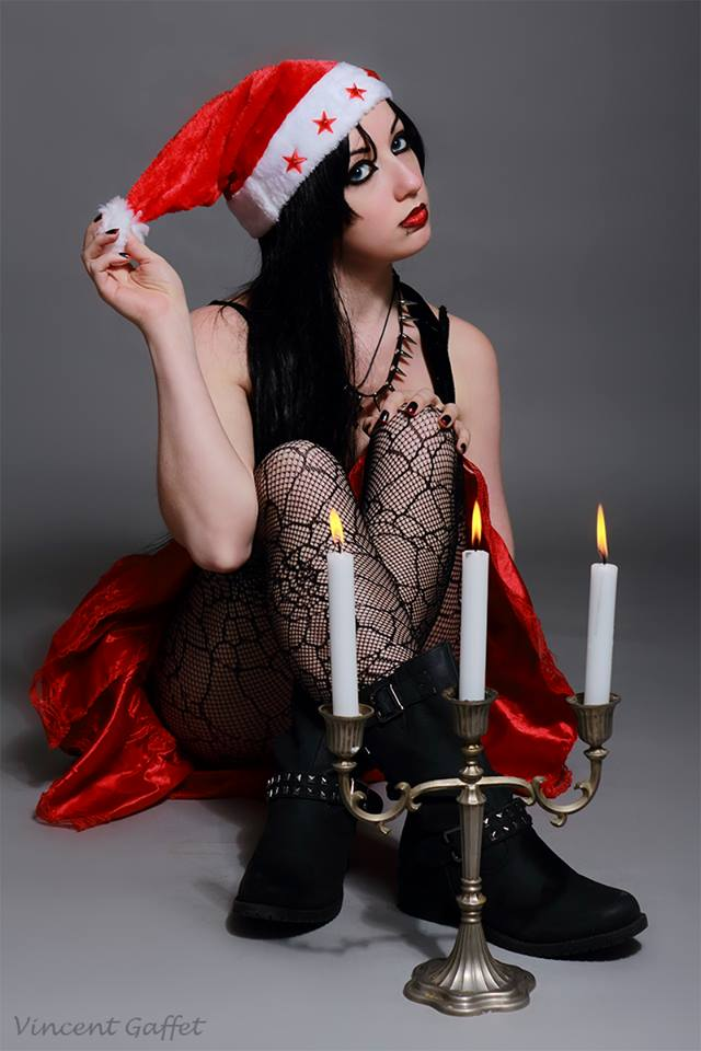Christmas goth sitting in front of three candle candelabra