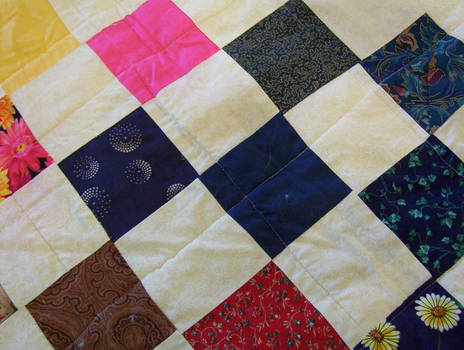 Quilt with pink blue brown and green patches