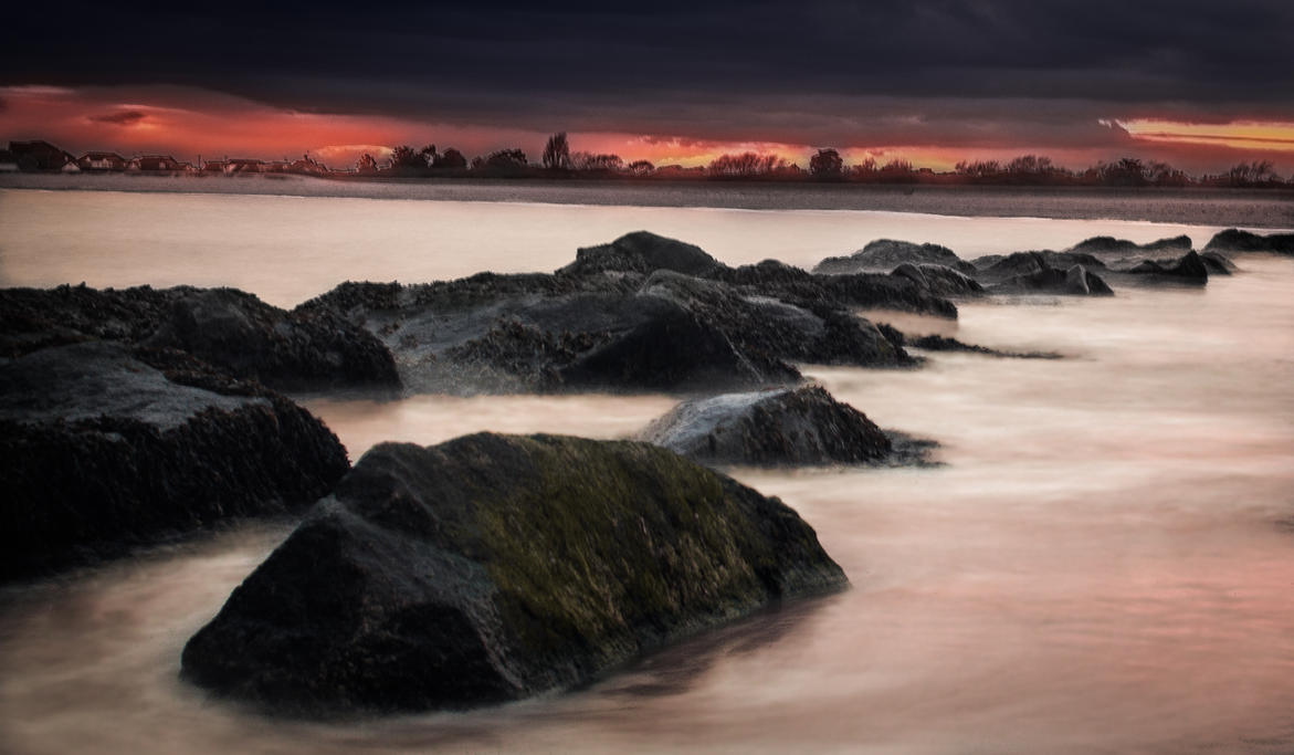 The Line Of Rocks And Stormy Sky by BradleyDeano