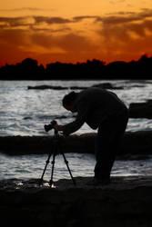 A photographer at sunset by strangetofla