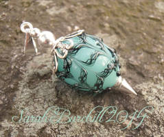 Mint green egg pendant with black lace by WeirdWondrous
