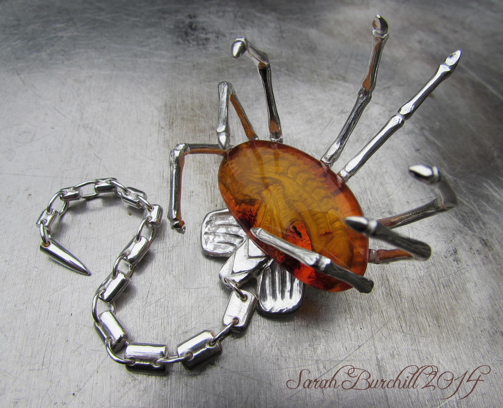 Facehugger silver brooch with amber carving