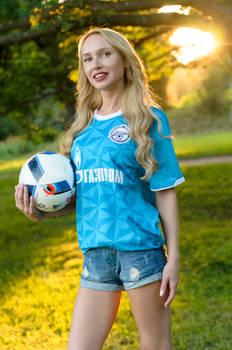 Football girl with ball sunset
