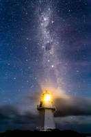 A lighthouse under the milky way
