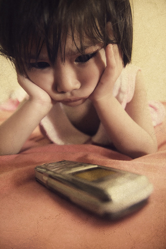 Young child staring at phone.