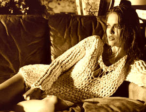 Em Lays On the Couch In A Cable Knit Sweater