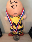 Charlie Brown pillow doll w/gold medal around it