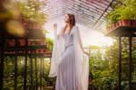An elf in a greenhouse in a white dress. Elf girl