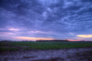 Stormy sky over field at sunset HDR by Archangelical-Stock