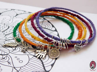 Yarn bracelets with silver charms by BlitheMagic